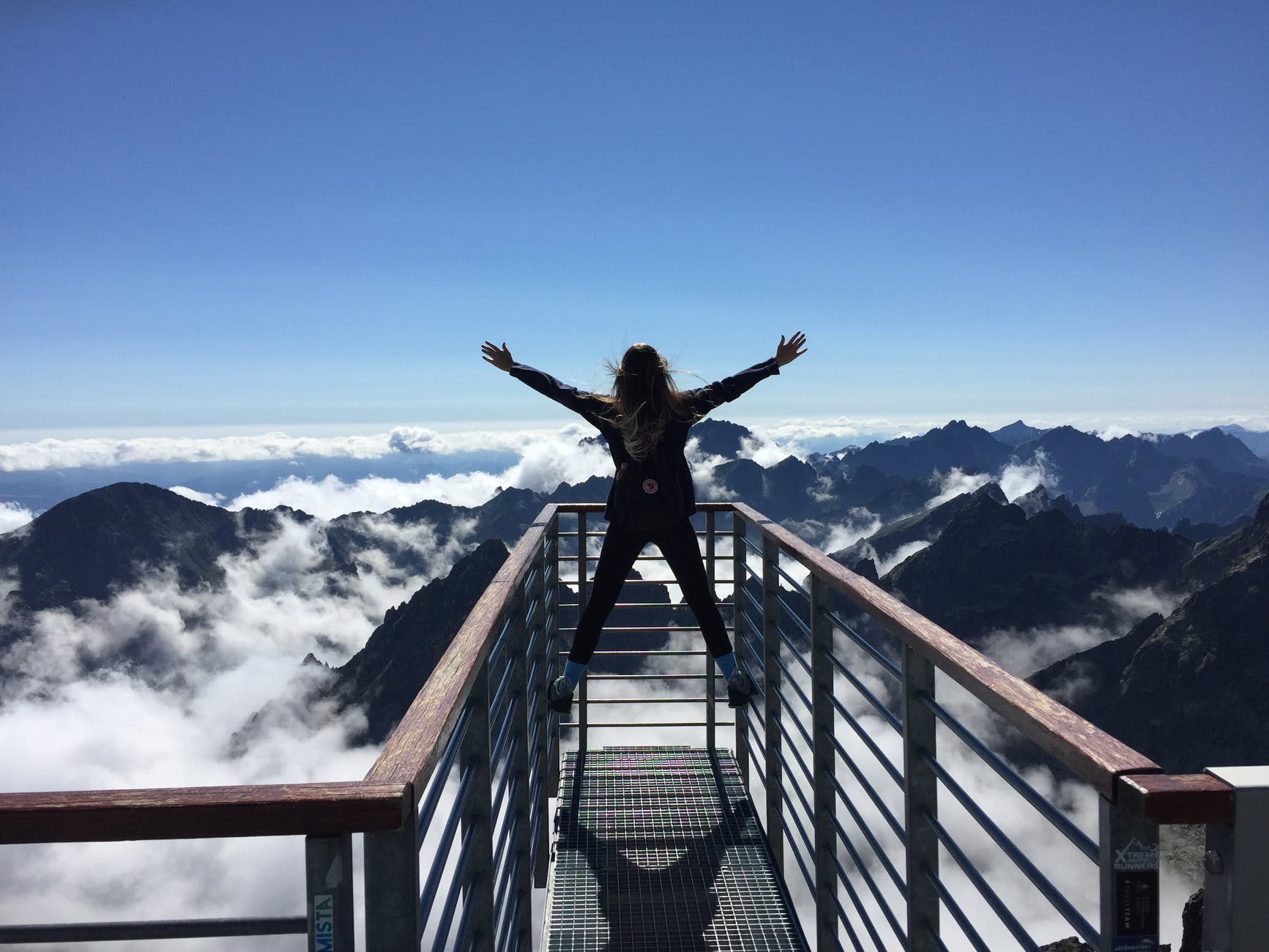 person standing on hand rails with arms wide open facing the mountains and clouds Photo by Nina Uhlu00edkovu00e1 on Pexels.com